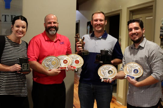 The team at Keaty Real Estate holds their REALTOR Association of Acadiana's Gumbo Cook-Off trophies.