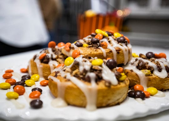 Chef and author Andrea LeTard's Halloween Candy Cinnamon Rolls covered in frosting, Kit Kats and Reese's Peanut Butter Cups and Reese's Pieces on top for extra color.