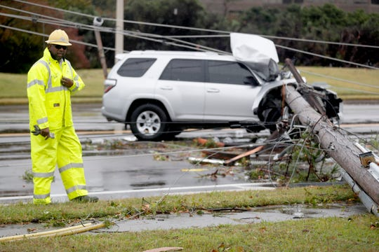 A Memphis Light, Gas and Water employee surveys the scene where a utility pole hit a vehicle on American Way near Thousand Oaks Boulevard on Monday, Oct. 21, 2019, in Memphis.