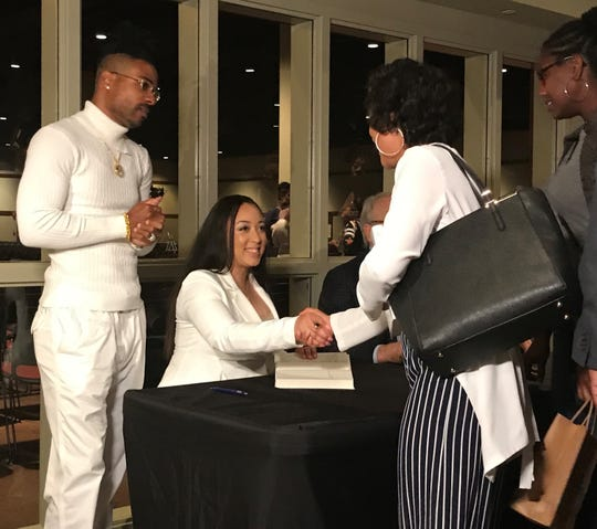 """Cyntoia Brown-Long (middle) signs copies of recently released memoir """"Free Cyntoia: My Search for Redemption in the American Prison System"""" beside husband Jamie Long (left) after speaking engagement at New Direction Christian Church on Oct. 20, 2019."""