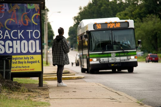 A rider waits to board a bus at a MATA stop on Poplar Ave. near Cleveland.