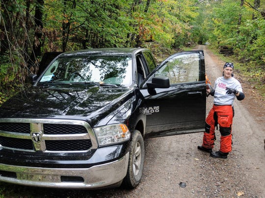 "Breanne Durovic, a volunteer with Team Rubicon, checks with a colleague as the nonprofit group worked this month to clear the edges of a snowmobile trail of fallen trees in the Chequamegon-Nicolet National Forest. ""You want to be able to help your neighbors out,"" said Durovic, who lives in Chicago. The area was devastated by windstorms July 19 and 20. Reopening snowmobile trails is considered vital to the rural region's economy."