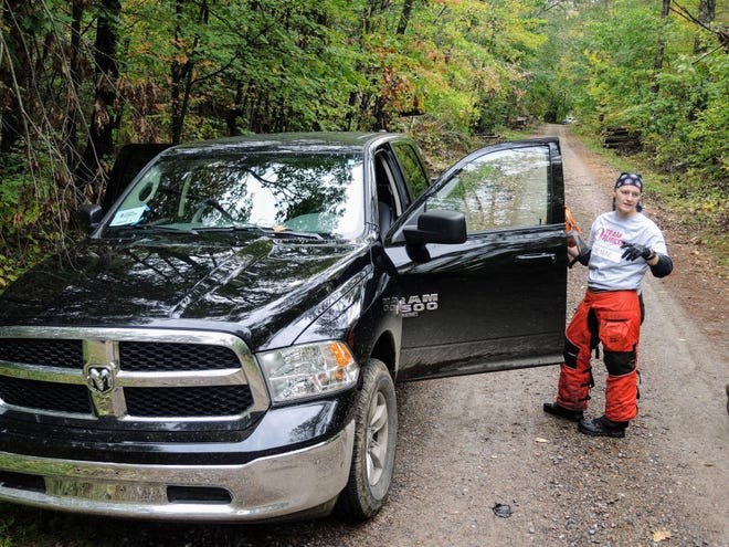 """Breanne Durovic, a volunteer with Team Rubicon, checks with a colleague as the nonprofit group worked this month to clear the edges of a snowmobile trail of fallen trees in the Chequamegon-Nicolet National Forest. """"You want to be able to help your neighbors out,"""" said Durovic, who lives in Chicago. The area was devastated by windstorms July 19 and 20. Reopening snowmobile trails is considered vital to the rural region's economy."""