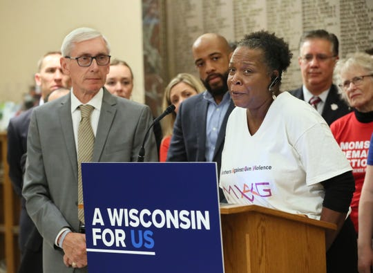 Governor Tony Evers, left and Lieutenant Governor, Mandela Barnes, second from left, listen as Debra Gillispie speaks about the day in 2003 she found out her son, Kirk Bickham Jr. was killed, becoming another victim of gun violence. Gov. Tony Evers held a press conference at Milwaukee City Hall signing an executive order calling a special session on gun laws.