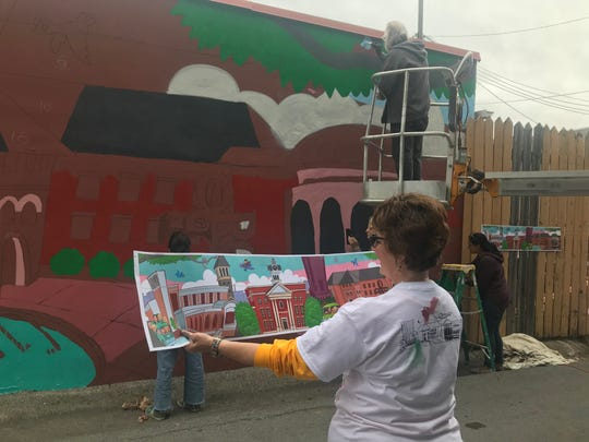 Susan Gulley with Carpe Artista arts program holds a rendering of what the mural on Vine Street will look like once it's finished. A group of community members worked on the project Oct. 19, 2019.