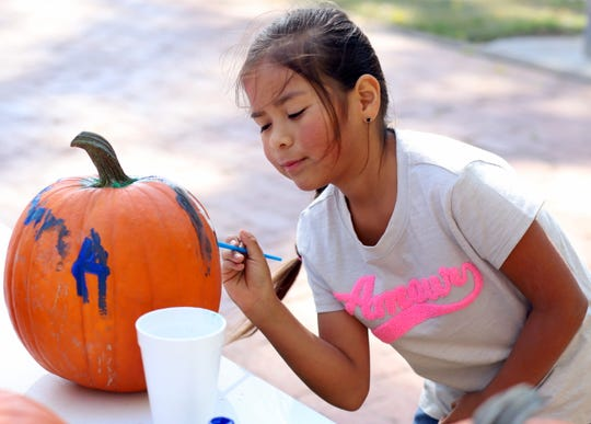 Emma Smith, 6, of las Cruces, NM, puts the finishing touches on her painted pumpkin.