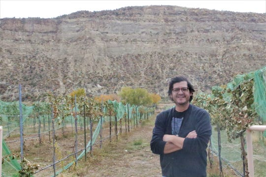 Tim Martinez, head winemaker at Rio Suave Vineyard, stands next to the grapes he uses to make hybrid wines in Blanco on Oct. 18, 2019.