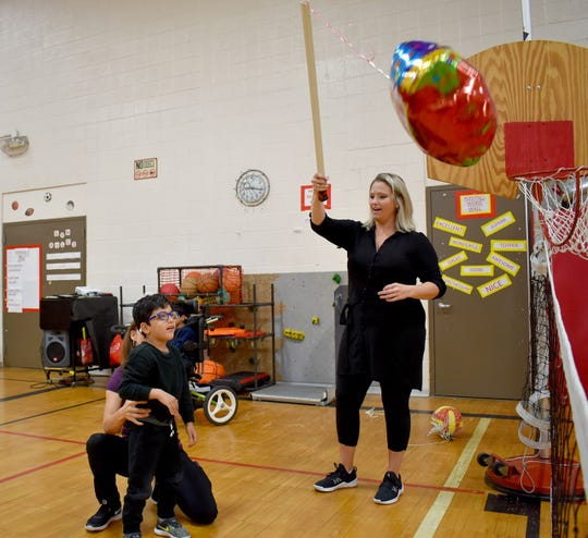 Cooke School adaptive physical education teacher Elizabeth Adams works with a student Monday morning.