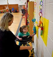Cooke School adaptive physical education instructor Elizabeth Adams works with a student Monday morning.