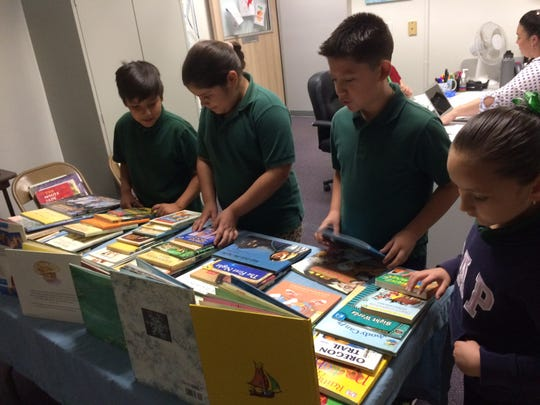 Students select their favorite books to read.