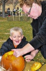 Luke Jordan 4, of Dayton smiles excitedly as his mother Rebecca Jordan carves a pumpkin for him.