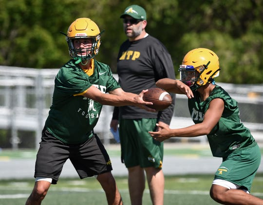 Manogue quaterback Drew Scolari hands the ball off during practice on Aug. 12.