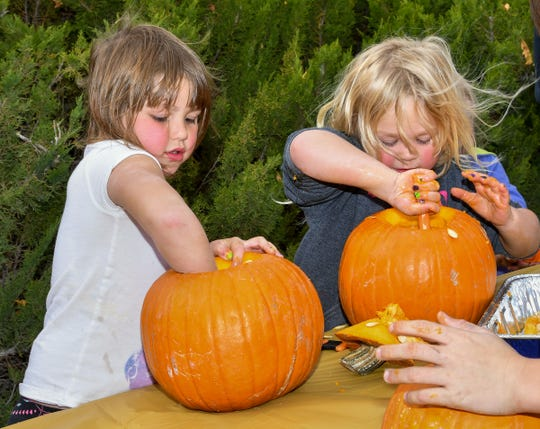 Cyriah Thomas, 5, and Cheyenne Thomas, 4, of Dayton, carve pumpkins at Fort Churchill's All Hallow's Eve event Saturday.