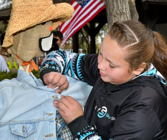Aubrey Conway, 12, of Yerington buttons a jacket on a scarecrow.