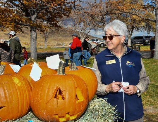 Linda Sanderson, a park volunteer, judges the jack-o-lantern contest.