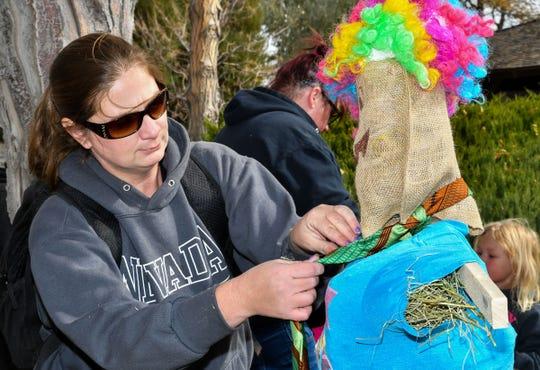 Kelly Neurenburg of Reno makes final touches to a scarecrow.