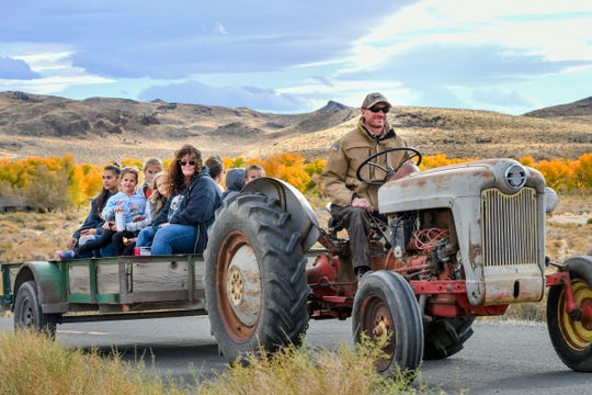 Park ranger Tom Gonzalez drives an old tractor pulling visitors on a hay ride through the Fort Churchill park.