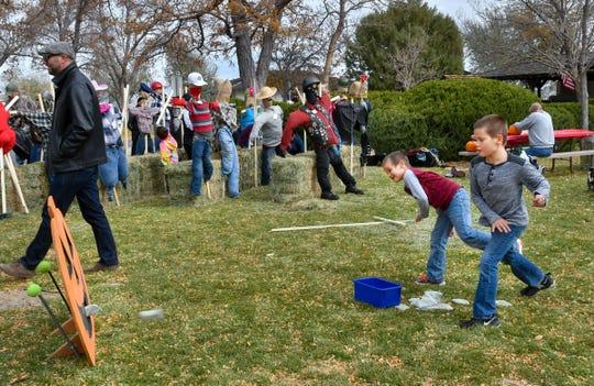 Landon Windsor, 10, right, and Gavin Windsor, 8, of Dayton throw beanbags at a wooden jack-o-lantern.