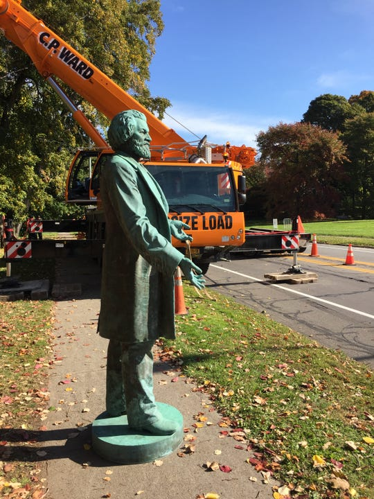 A bronze statue of Frederick Douglass, which for decades has called Highland Park Bowl home, rests on a sidewalk during a move to a more visible spot on South Avenue at Robinson Drive.
