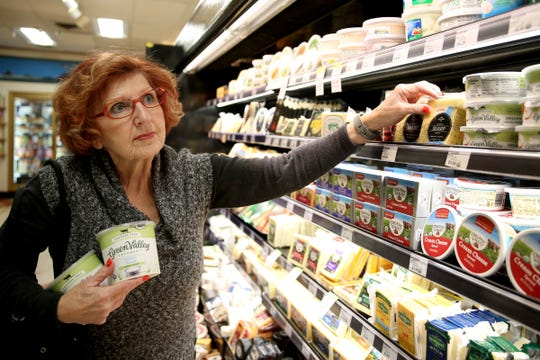 Sandi Durham, of Keizer, looks over the cheese selection at LifeSource Natural Foods in Salem on Oct. 21, 2019. A 25% tariff is now in effect for imported specialty food items from certain European countries.