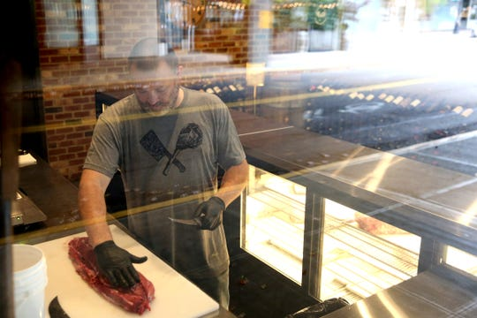 Adam Arana, the butcher shop manager, trims a tenderloin before cutting it into filet mignon steaks at Rudy's Butcher Shop, open across the street from Rudy's Steakhouse in downtown Salem on Oct. 21, 2019.