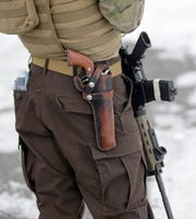 In this Jan. 9, 2016, file photo, a man stands guard after several organizations arrived at the Malheur National Wildlife Refuge near Burns, Ore.