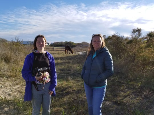 "Zoe Newman, left, and her mother Sam stand with the bay stallion ""Delegate's Pride,"" also known as ""Chip,"" during a recent trip to Assateague Island. The 10-year-old pony received the nickname because people feel he takes after his father and is a ""chip off the old block."""