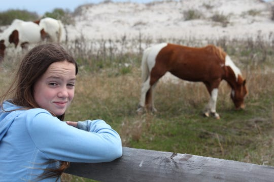 Zoe Newman with her first foster horse, Annie Laurie, during a recent trip to Assateague Island. Zoe recently became the first person to foster the entire Maryland herd of ponies.