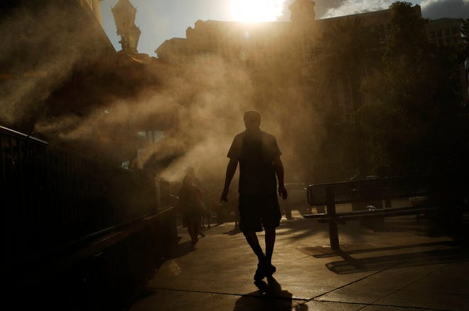 "File - In this July 26, 2018, file photo, a man cools off in a water mist along the Las Vegas Strip in Las Vegas. Planners in Las Vegas say they're working to reduce rising temperatures in a city where paved areas create a warmer environment than plant-covered or rural desert areas. The Las Vegas Sun reports that a panel on Oct. 15, 2019, considered a recent Urban Land Institute finding that Las Vegas is the most intense ""urban heat island"" in the U.S. That's after another group reported in April that average temperatures in Las Vegas have risen faster than any other city since 1970. (AP Photo/John Locher, File)"