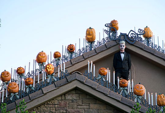 Dixie State professor Josh Pedersen stands atop his completed Haunted Mansion roofline inspired by Disney's 'Nightmare Before Christmas'.