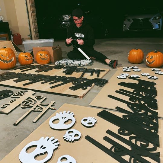 Josh Pedersen working with PVC pipe and laser cut swirls for the roof of his 'Haunted Mansion' Halloween house in St. George.