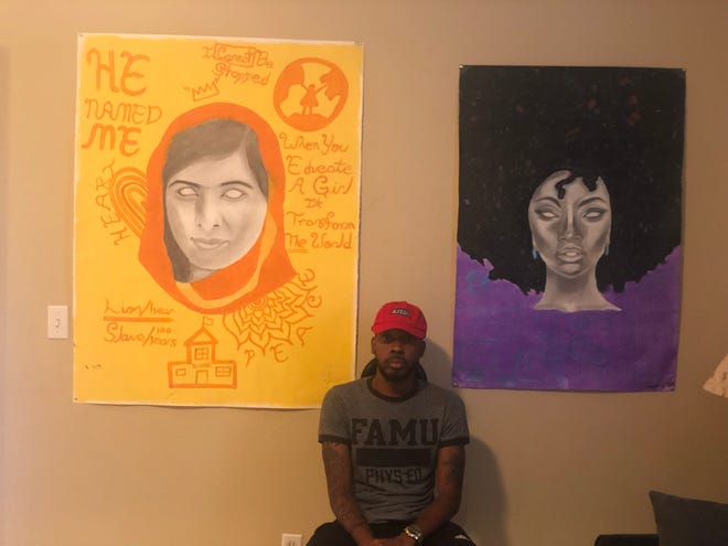 Denzel Goldwire sitting between Malala Yousafzai and and African American female with her natural hair.