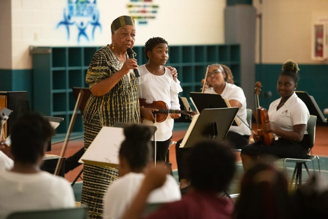 Dr. Crystal Bujol, standing left, with Mieca-eeja Ferguson, talks to the audience at the American Black History program featuring the Gifford Youth Orchestra at the Gifford Community Center on Feb. 23, 2019.