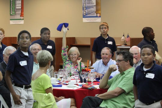 "Dottie LeClair, center, raises her handkerchief to answer a question while her husband, D'Arcy and Samaritan Center for Young Boys & Families residents Darion, Christian, Cameron, Josh and Jonathan look on during a previous ""Are You Smarter than a 5th Grader?"" fundraiser for the center in Stuart."