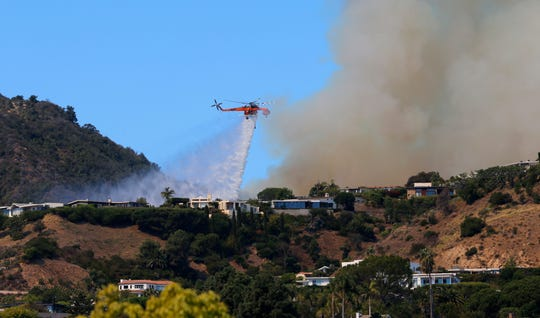 A helicopter makes a water drop as flames threaten homes on a ridgeline in the Pacific Palisades area of Los Angeles, Monday, Oct. 21, 2019. (AP Photo/Reed Saxon)