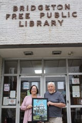 Linda McFadden, director, Bridgeton Public Library, and photographer Gil Walter display a sample from the new display of photographs of Cumberland County at the library at 150 E. Commerce St. Walter donated the framed photographs to the library for display and sale with proceeds to benefit the library.