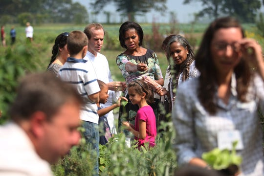 Former First Lady Michelle Obama talks with Executive Chef of Blue Hill restaurant Dan Barber (2nd L) in 2010 as she tours the herb garden with first ladies from various countries.