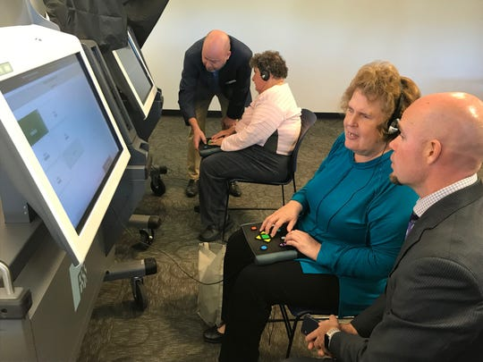Disabled voter Carole Conklin, third from the left, being instructed on how to use voting technology.