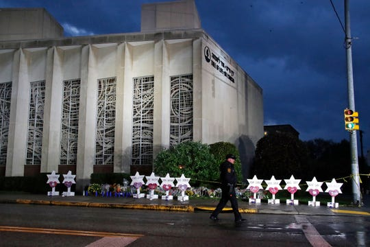 FILE - In this Oct. 28, 2018, file photo a Pittsburgh Police officer walks past the Tree of Life synagogue and a memorial of flowers and stars in Pittsburgh, in remembrance of those killed and injured when a shooter opened fire during services at the synagogue. A Jewish civil rights group says at least a dozen white supremacists have been arrested on allegations of plotting, threatening or carrying out anti-Semitic attacks in the U.S. since the massacre at the Pittsburgh synagogue in 2018. (AP Photo/Gene J. Puskar, File)