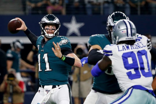 Philadelphia Eagles quarterback Carson Wentz (11) throws a pass under pressure from Dallas Cowboys defensive end Demarcus Lawrence (90) in the first half of an NFL football game in Arlington, Texas, Sunday, Oct. 20, 2019.