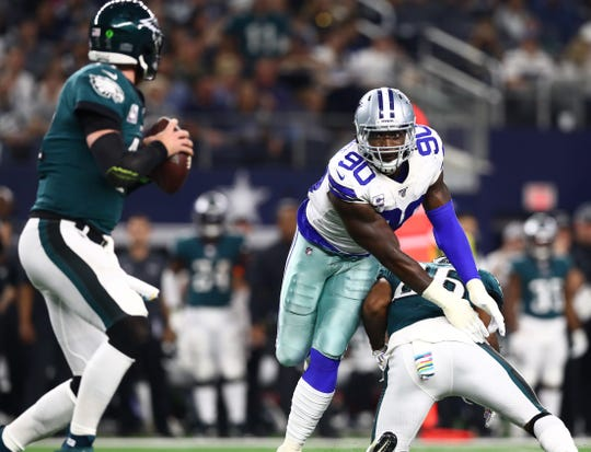 Oct 20, 2019; Arlington, TX, USA; Philadelphia Eagles quarterback Carson Wentz (11) is pressured in the pocket by Dallas Cowboys defensive end DeMarcus Lawrence (90) at AT&T Stadium.