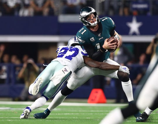 Philadelphia Eagles quarterback Carson Wentz (11) is sacked in the second quarter by Dallas Cowboys cornerback Jourdan Lewis (27) at AT&T Stadium in Arlington, Texas, on Sunday, Oct. 20, 2019.