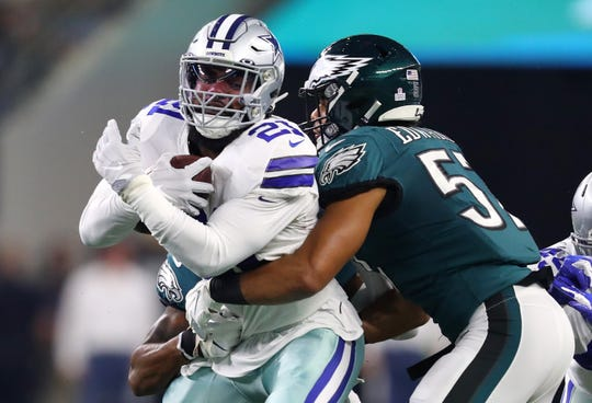 T.J. Edwards #57 and Rodney McLeod #23 of the Philadelphia Eagles attempt to tackle Ezekiel Elliott #21 of the Dallas Cowboys in the game at AT&T Stadium on October 20, 2019 in Arlington, Texas.