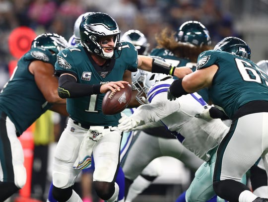 Oct 20, 2019; Arlington, TX, USA; Philadelphia Eagles quarterback Carson Wentz (11) scrambles under pressure in the third quarter against the Dallas Cowboys at AT&T Stadium.