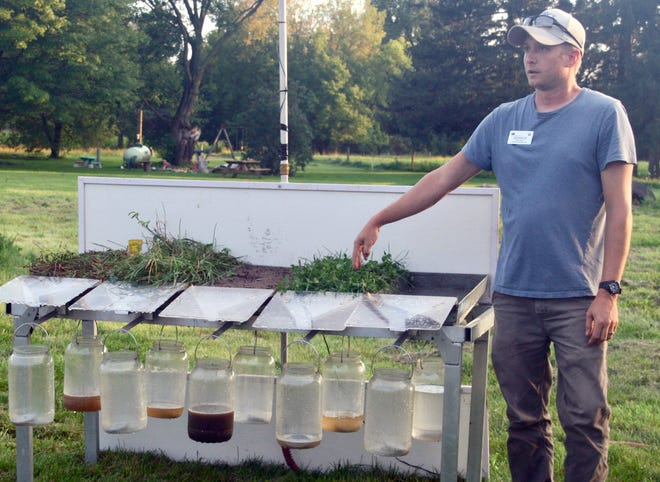 NRCS soil conservationist Derrick Raspor used a rainfall simulator to demonstrate different cropping systems react to water runoff.