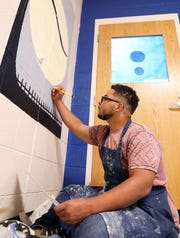 "Tyler Parker, a junior at Maysville High School, paints the cover of ""To Kill a Mockingbird"" outside a classroom."