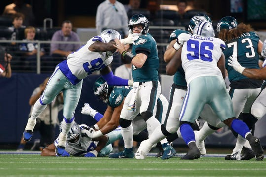 Cowboys defensive end Demarcus Lawrence (90) sacks Eagles quarterback Carson Wentz (11) and causes a fumble in the first quarter at AT&T Stadium.