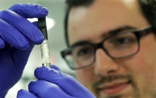 In this July 19, 2019, file photo, Pierce Prozy examines a Yolo! brand vape oil cartridge marketed as a CBD product at Flora Research Laboratories in Grants Pass, Ore.