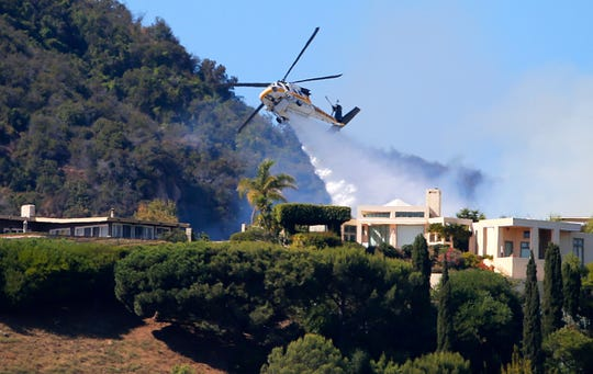 A Los Angeles County Fire Department helicopter makes a water drop as flames from a wildfire threaten homes on a ridgeline in the Pacific Palisades area of Los Angeles on Monday.