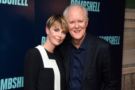"Charlize Theron and John Lithgow participate in the ""Bombshell"" cast photo call at the Crosby Street Hotel on Oct. 20, 2019, in New York."